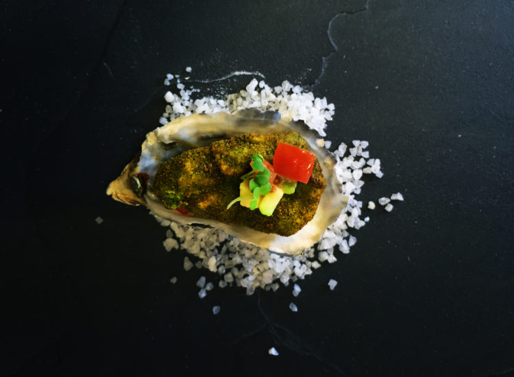 Oyster deep fried with herb panko crumbs served on tomato and avocado salsa