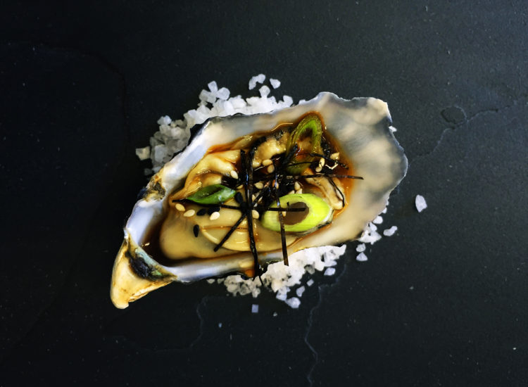 Oyster with Asian sesame citrus dressing, nori strips, sliced spring onions and toasted sesame seeds